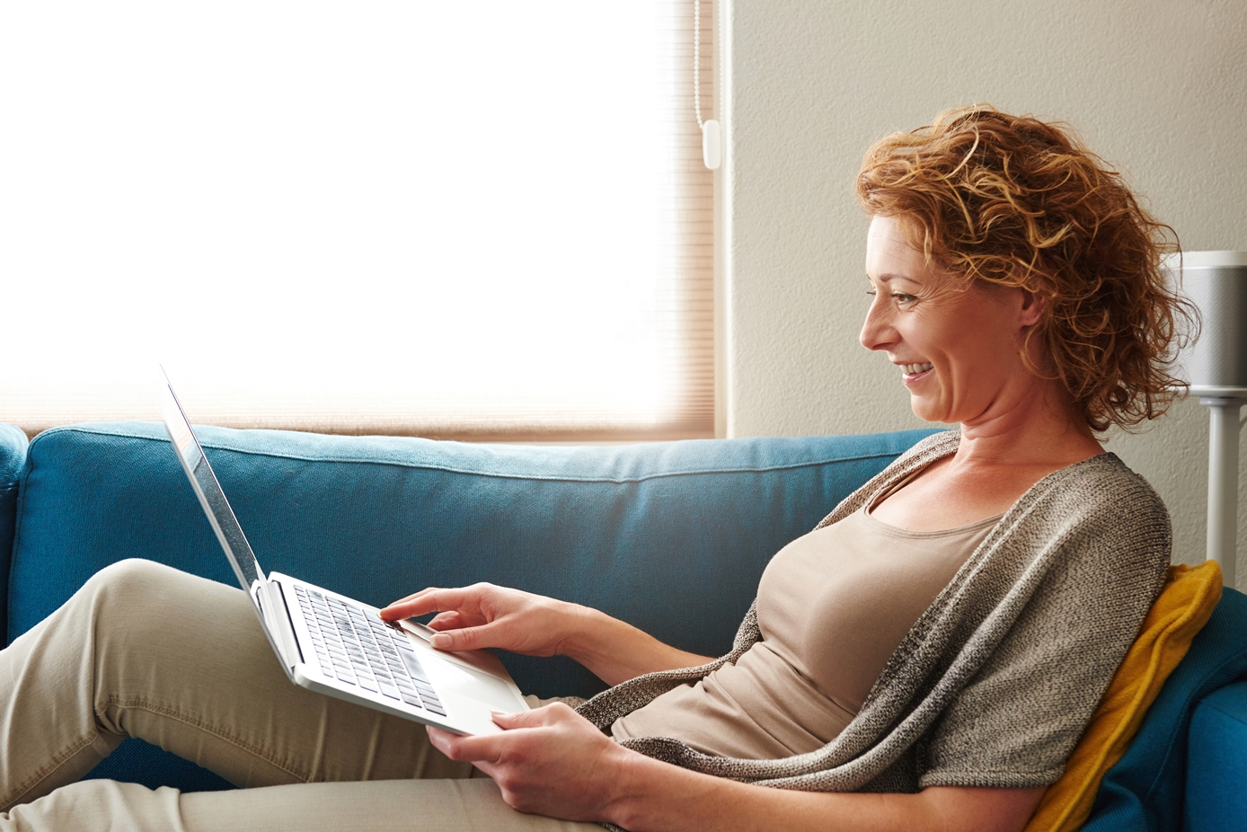 Woman lying on sofa with laptop smiling